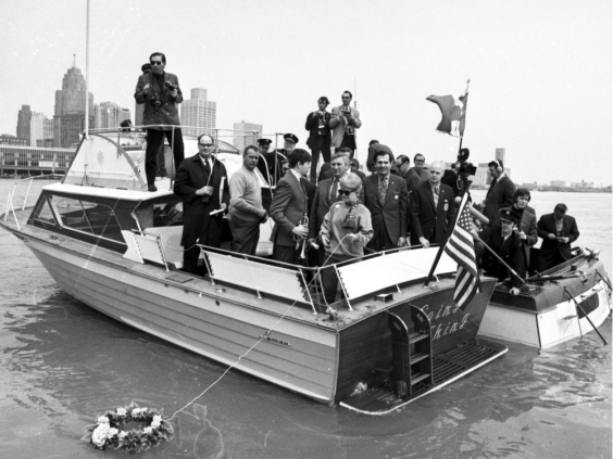 "Mourning a death. Autoworkers on boats from both sides of the border, including members of the United Auto Workers' Downriver Anti-Pollution League, hold a wake on the Detroit River on the first Earth Day, April 22, 1970, and lay a floral wreath to signify the ""death"" by pollution of the river and Lake Erie"